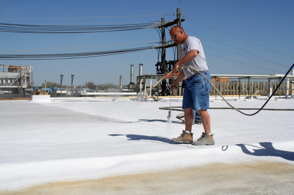 Roofer applying spray foam commercial roofing