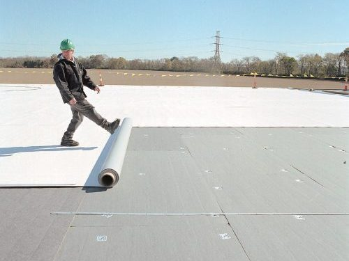 Fabric-reinforced membrane roofing installation.